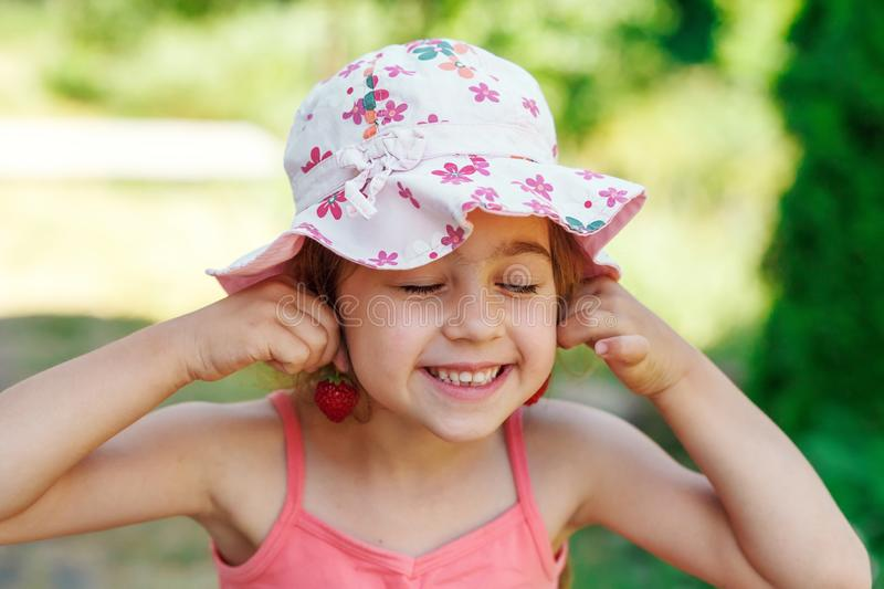 Portrait of Cute little girl in big hat is eating strawberries at summer day stock photos
