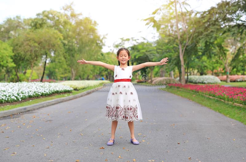Portrait of happy little girl closed eyes and open wide her arms standing on road in the garden royalty free stock photos