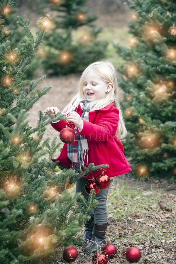 Portrait of happy little girl hanging baubles on tree at farm stock photo