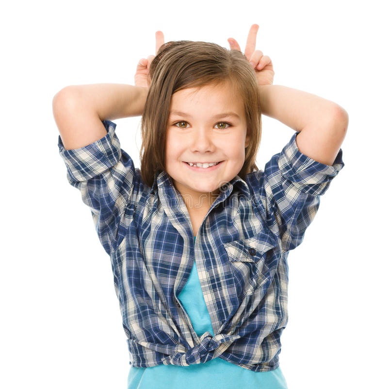 Portrait of a happy little girl. Laughing and making horns or bunny ears, isolated over white royalty free stock images