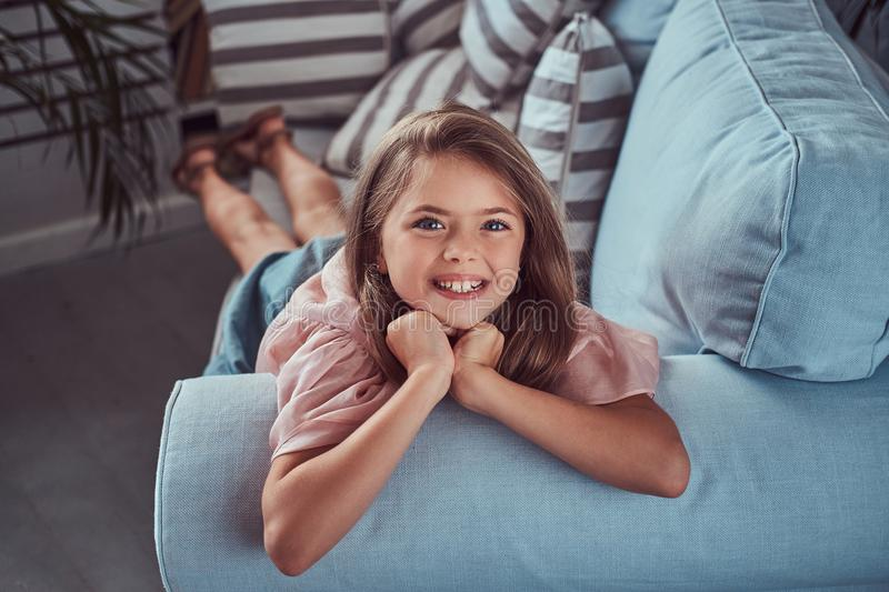 Portrait of a happy little girl with long brown hair and charming smile, looking at a camera, lying on a sofa at home stock photo
