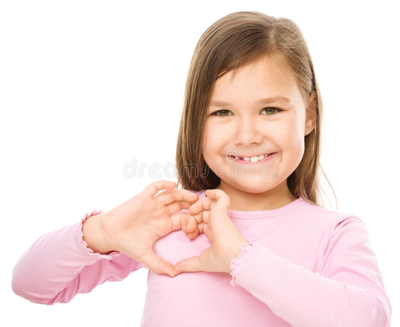 Portrait of a happy little girl. Showing heart gesture, isolated over white royalty free stock images