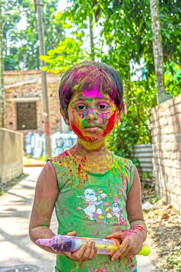 Portrait of happy little girl smeared with holi powder color stock image