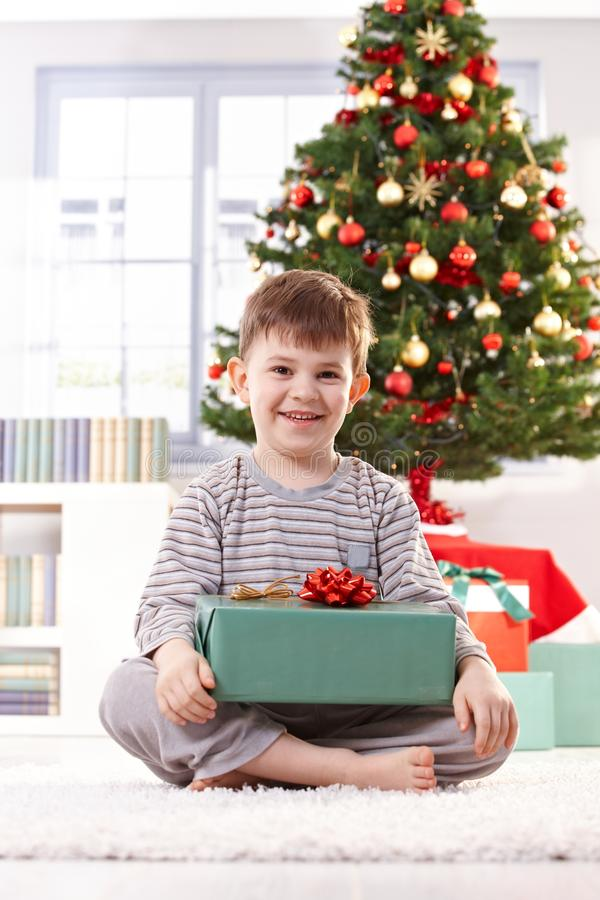 Portrait of happy little kid in christmas morning. Portrait of happy little kid sitting in pyjama in christmas morning holding gift parcel, smiling at camera royalty free stock photo