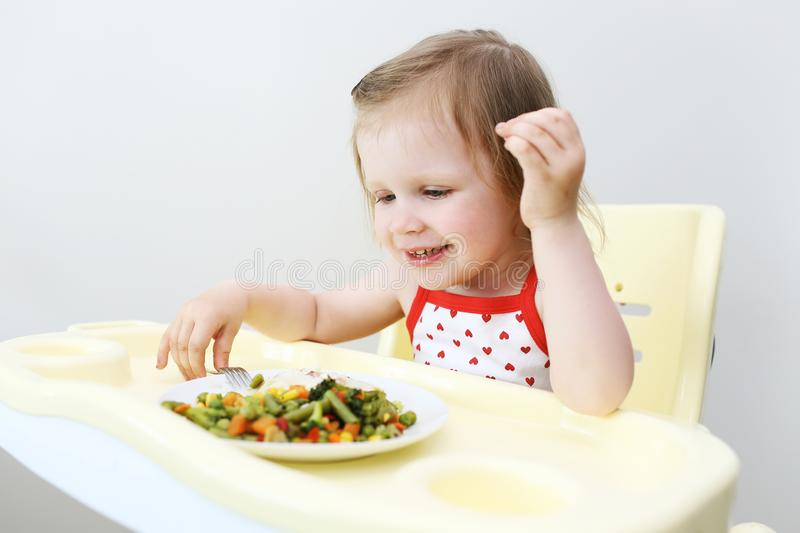 Portrait of happy little 2 years girl eating fish with vegetable stock images
