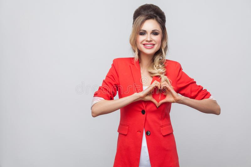 Portrait of happy in love beautiful business lady with hairstyle, makeup in red fancy blazer, standing with love gesture and. Looking at camera with love royalty free stock photography