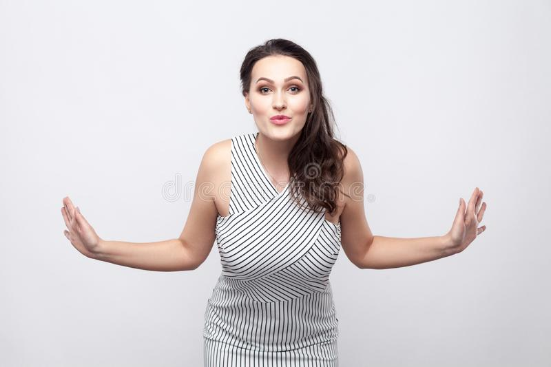 Portrait of happy lovely beautiful young brunette woman with makeup and striped dress standing with crossed arms and looking at royalty free stock images