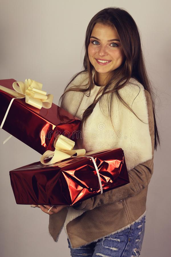Portrait of a happy lovely young woman holding gift box stock photos