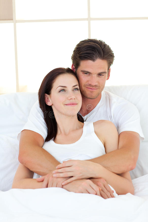 Portrait of happy lovers hugging in their bed. Concept of love royalty free stock photography