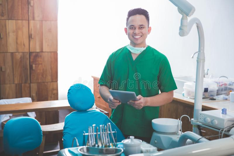 Male dentist in the clinic using tablet. Portrait of happy male dentist using tablet while in the clinic stock photos