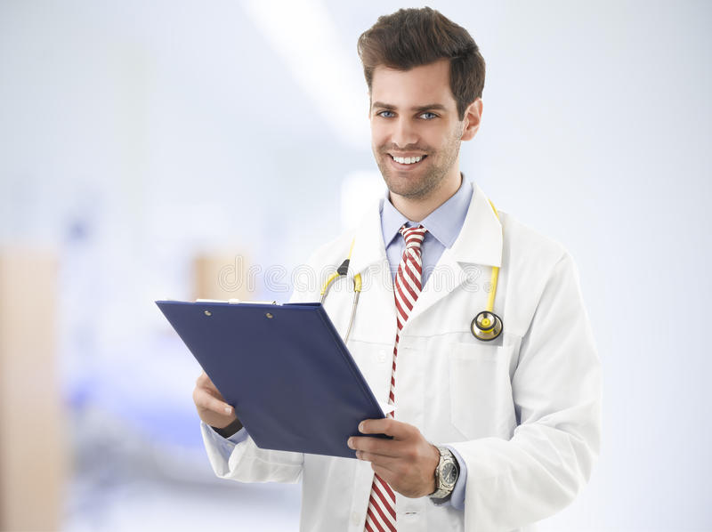 Portrait of happy male doctor with clipboard royalty free stock photo