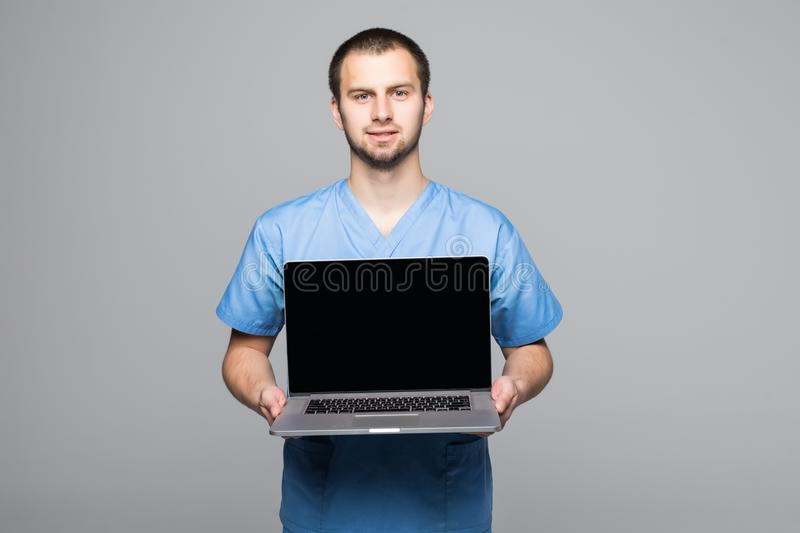 Portrait of a happy male doctor dressed in uniform with stethoscope showing blank screen laptop computer isolated over gray backgr royalty free stock image