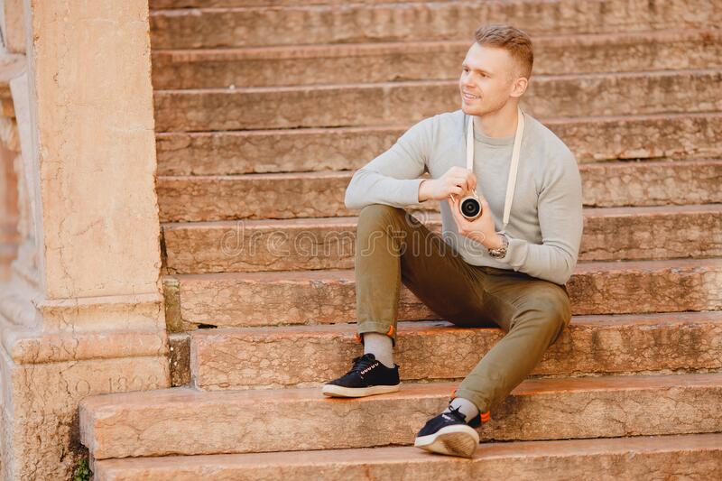 Portrait happy male traveler photographer holding camera in hands sitting on steps in italy, blurred background royalty free stock photography