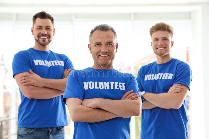 Portrait of happy male volunteers in uniform stock photos