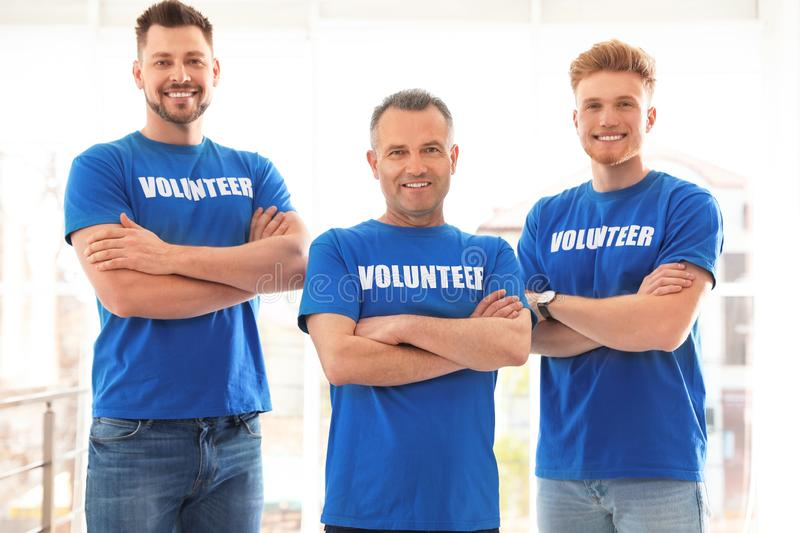 Portrait of happy male volunteers in uniform royalty free stock images