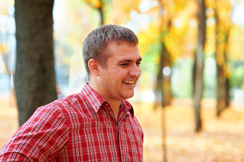 Portrait of happy man in autumn city park. Dressed in red plaid shirt. Bright yellow trees and leaves stock image