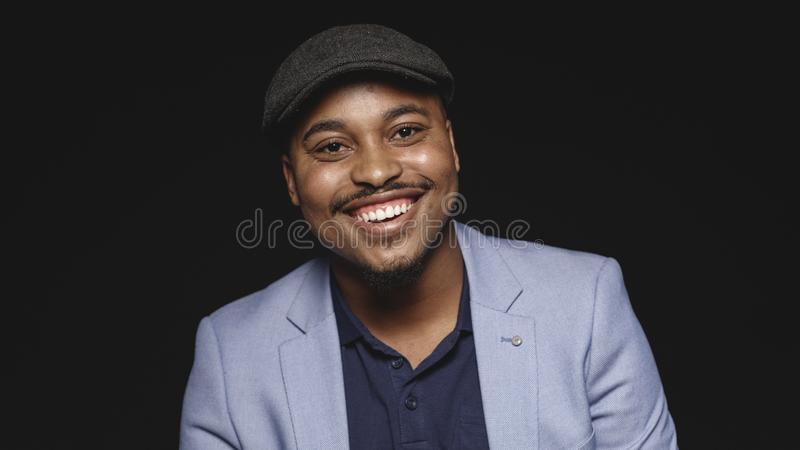 Portrait of a happy man in cap. Close up of smiling african american businessman isolated on black background. Cheerful man in suit and cap looking at camera stock photos