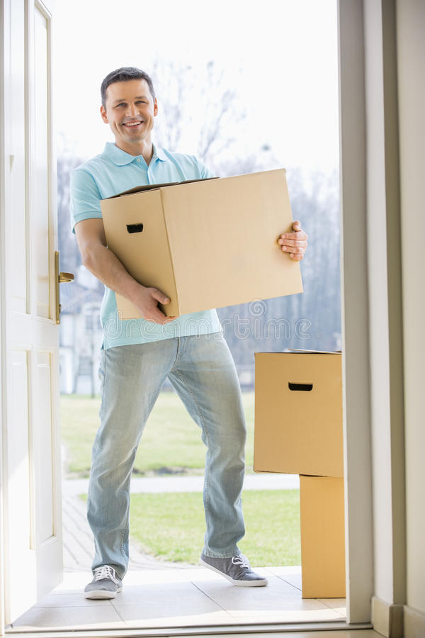Portrait of happy man carrying cardboard box while entering new home stock photo