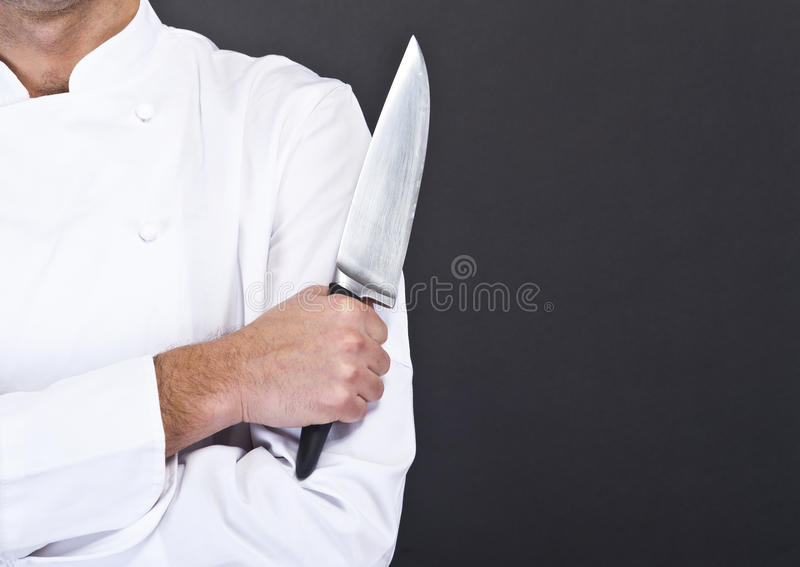 Portrait of happy man in cook uniform looking at camera. With knife royalty free stock photography