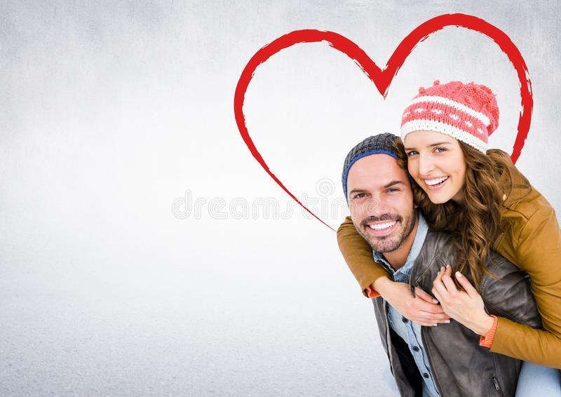 Portrait of happy man giving piggy back to woman against white background stock photography