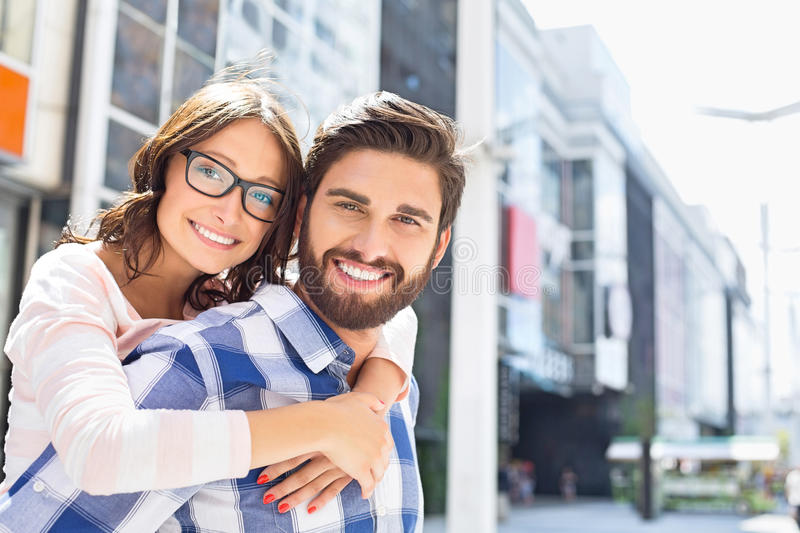 Portrait of happy man giving piggyback ride to woman in city stock image