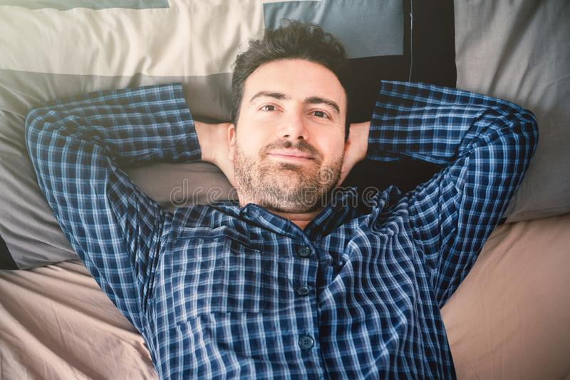 Portrait of happy man in his bed in the morning. Relaxed man lying in bed and feeling good royalty free stock photography
