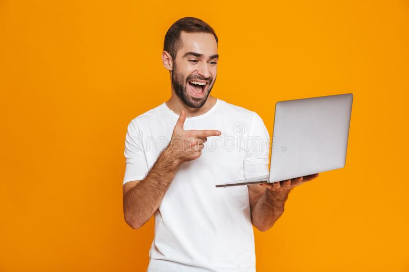 Portrait of happy man 30s in white t-shirt using silver laptop, isolated over yellow background royalty free stock image