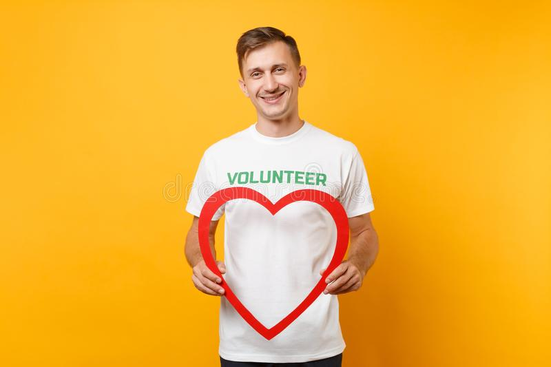 Portrait of happy man in white t-shirt with written inscription green title volunteer hold big red wooden heart isolated stock photography