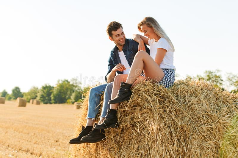 Portrait of happy man and woman sitting on big haystack in golden field, during sunny day. Portrait of happy men and women sitting on big haystack in golden royalty free stock photos