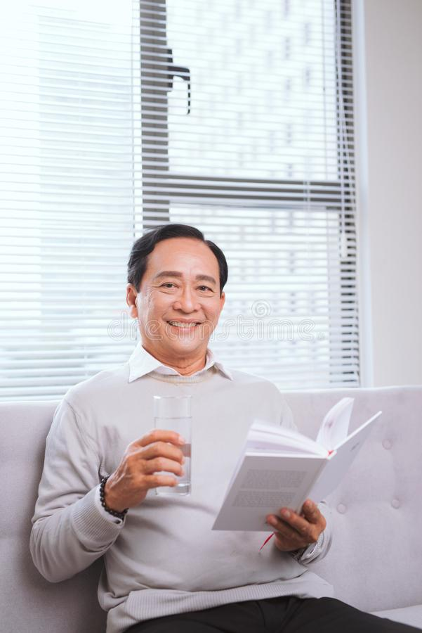 Portrait of an happy mature man reading a book relaxed at home. stock image
