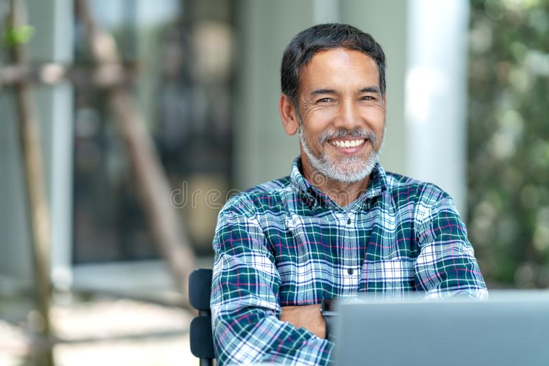 Portrait of happy mature man with white, grey stylish short beard looking at camera outdoor. Casual lifestyle of retired hispanic royalty free stock photos