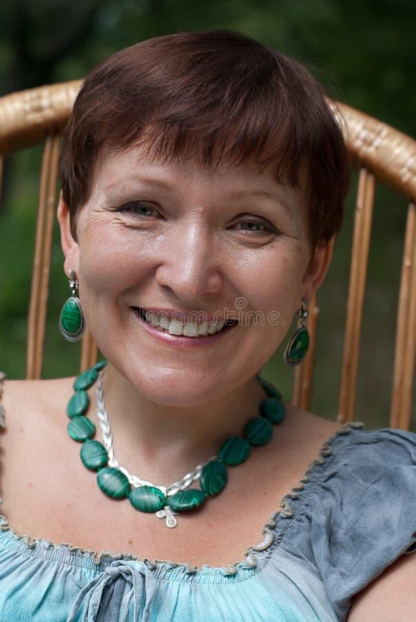 Portrait of happy mature woman in malachite bijou. Smiling stock images