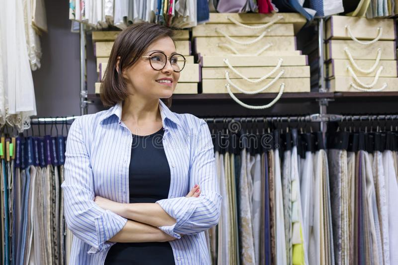 Portrait of happy mature woman owner with crossed arms in interior fabrics store, background fabric samples. Small business home t royalty free stock image