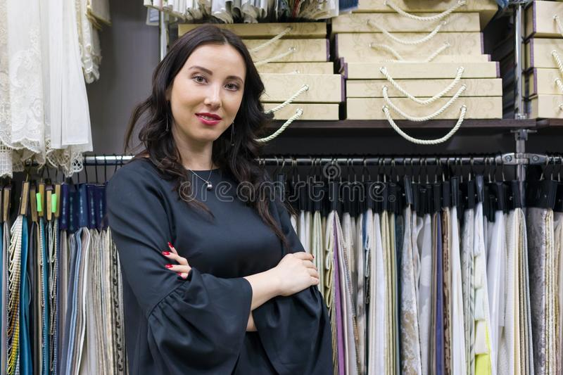 Portrait of happy mature woman owner with crossed arms in interior fabrics store, background fabric samples. Small business home t stock photography