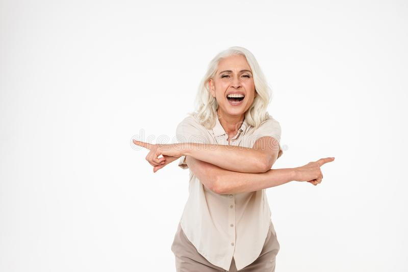 Portrait of a happy mature woman pointing fingers royalty free stock image