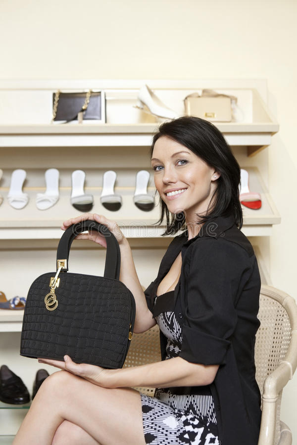 Portrait of a happy mid adult woman showing designer purse in shoe store. Portrait of a happy mid adult women showing designer purse in shoe store royalty free stock images