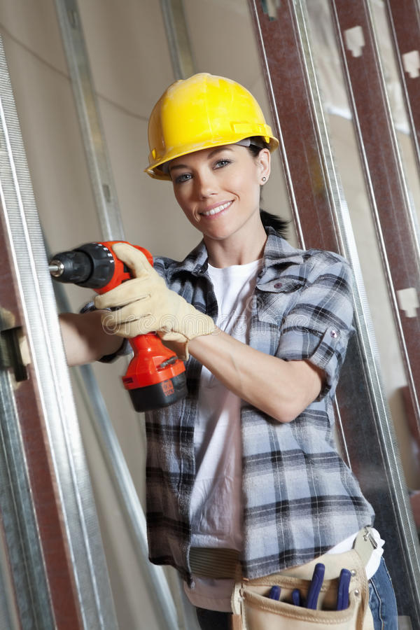 Portrait of a happy mid adult woman worker drilling at construction site stock images