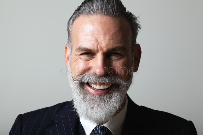 Portrait of happy middle aged bearded gentleman wearing trendy suit over empty gray background. Studio shot, business royalty free stock images