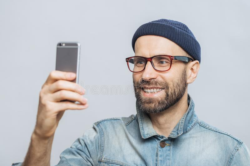 Portrait of happy middle aged smiling male wears denim jacket, hat and glasses, holds smart phone for making selfie, isolated over stock photo