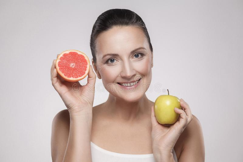 Portrait of happy middle aged woman with perfect face skin toothy smiling, holding fresh slice grapefruit and apple in her hands, stock image