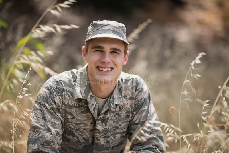 Portrait of happy military soldier crouching in grass royalty free stock photography