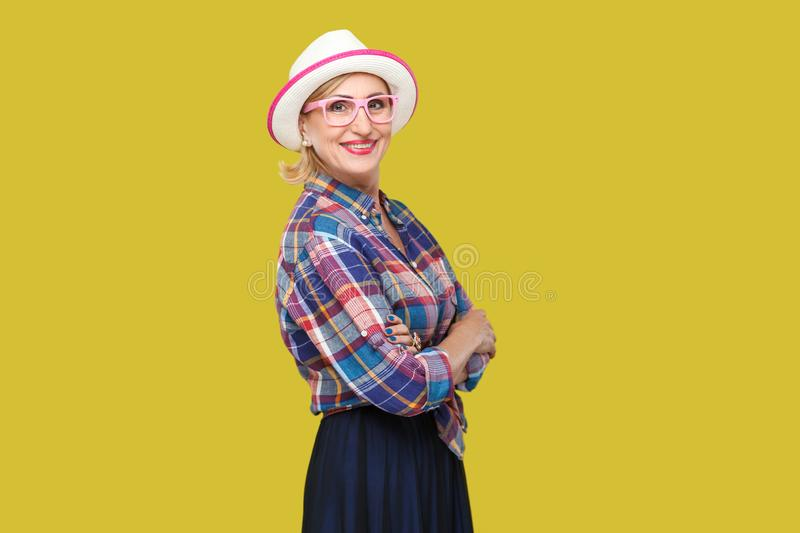 Portrait of happy modern stylish mature woman in casual style with hat and eyeglasses standing, crossed arms and looking at camera. With toothy smile. indoor stock photos