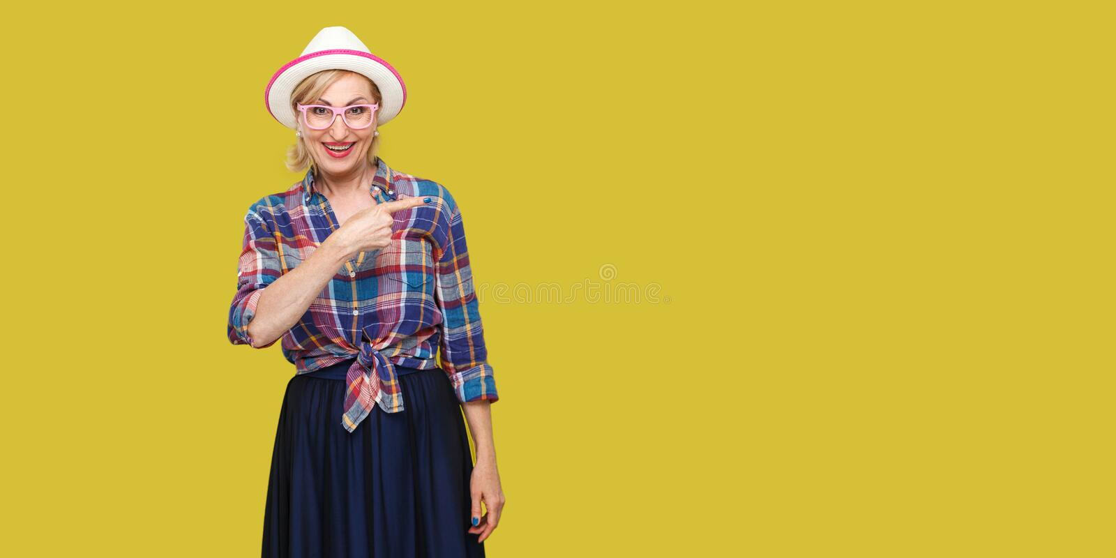 Portrait of happy modern stylish mature woman in casual style with hat and eyeglasses standing looking at camera and pointing and. Wall empty copyspace. indoor royalty free stock image