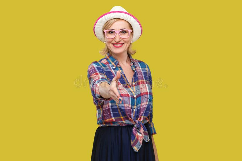 Portrait of happy modern stylish mature woman in casual style with hat and eyeglasses standing with toothy smile, looking and. Giving hand to greeting. indoor stock image