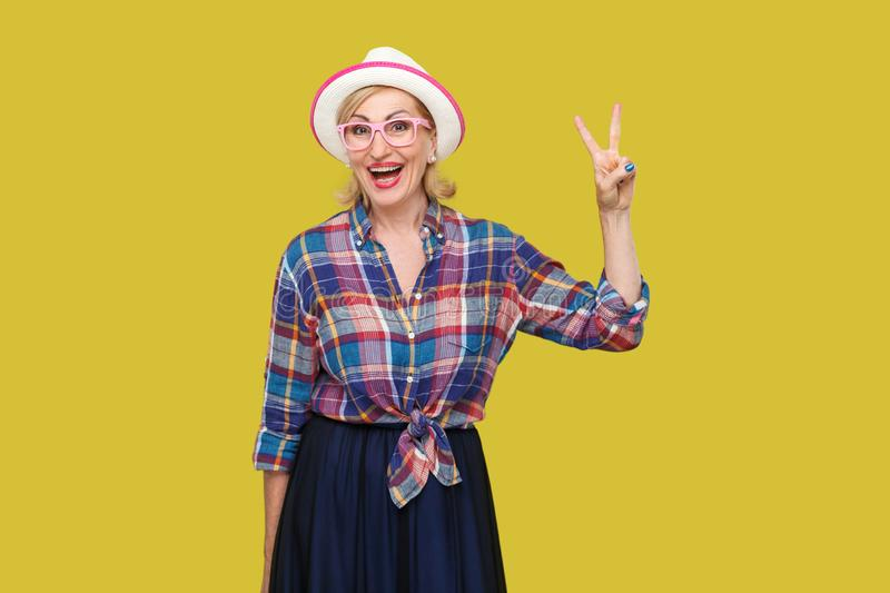 Portrait of happy modern stylish mature woman in casual style with hat, eyeglasses standing with victory or peace sign, looking at. Camera with toothy smile royalty free stock images