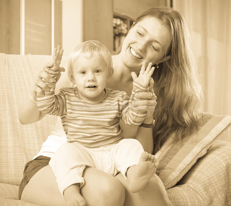 Portrait of happy mom with toddler. On sofa in home royalty free stock photo