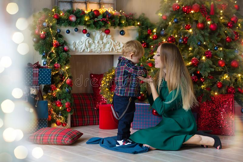 Portrait of happy mother and adorable baby celebrate Christmas. New Year`s holidays. Toddler with mom in the festively decorated royalty free stock image