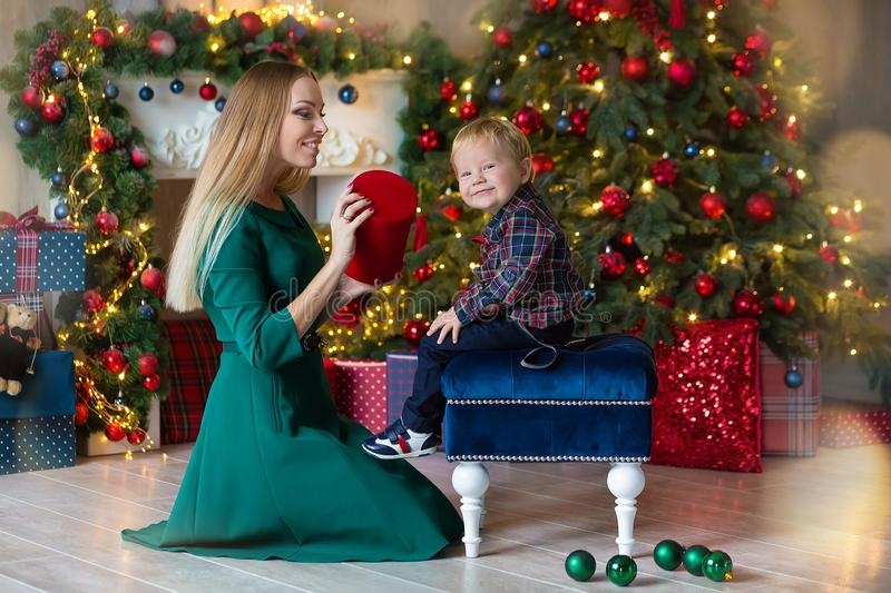 Portrait of happy mother and adorable baby celebrate Christmas. New Year`s holidays. Toddler with mom in the festively decorated stock photos