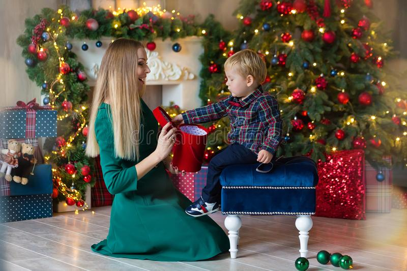 Portrait of happy mother and adorable baby celebrate Christmas. New Year`s holidays. Toddler with mom in the festively decorated stock photo