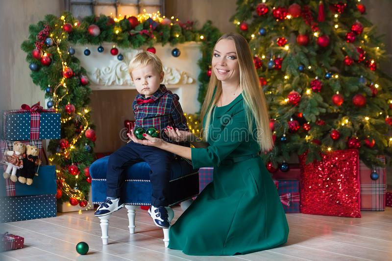 Portrait of happy mother and adorable baby celebrate Christmas. New Year`s holidays. Toddler with mom in the festively decorated royalty free stock photos